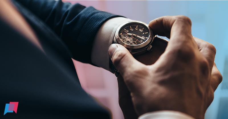 man kijkt op horloge